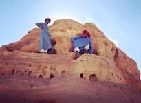 bedouin boys climbing a rock
